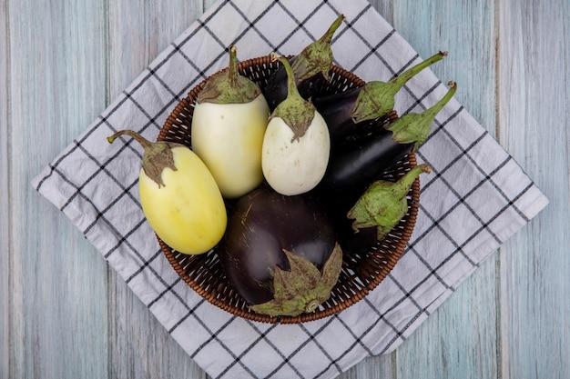 Bovenaanzicht van aubergines in mand op geruite doek op houten achtergrond