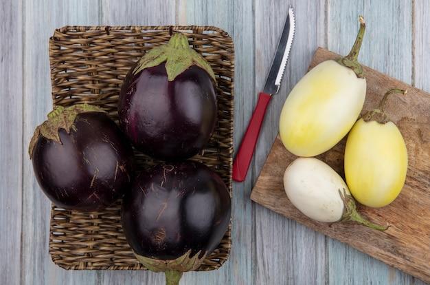 Bovenaanzicht van aubergines in mand plaat met gele en witte op snijplank en mes op houten achtergrond
