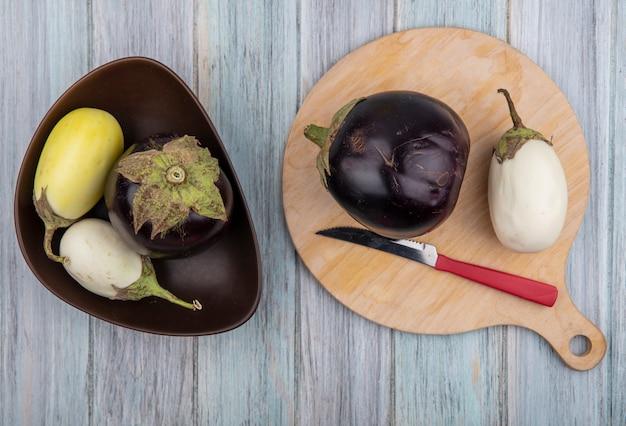 Bovenaanzicht van aubergines met mes op snijplank en in kom op houten achtergrond