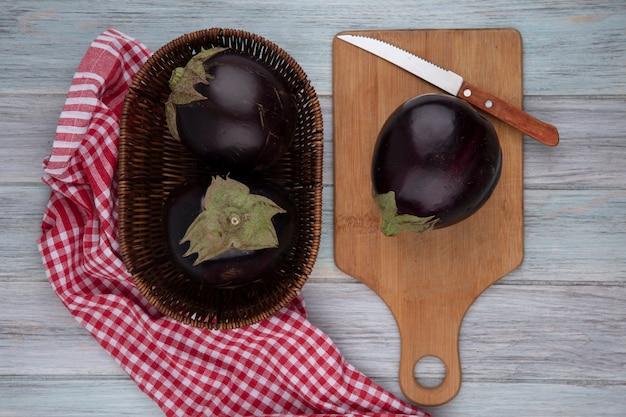 Bovenaanzicht van aubergines met mes op snijplank en in mand op geruite doek op houten achtergrond