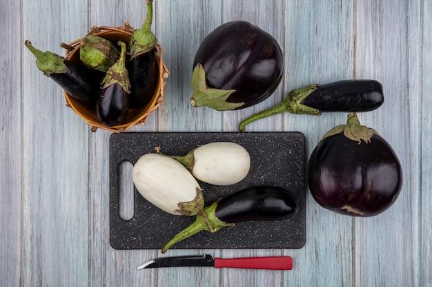 Bovenaanzicht van aubergines op snijplank en in mand met mes op houten achtergrond