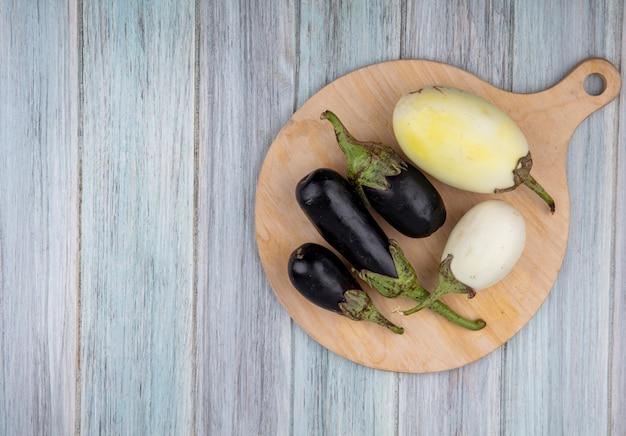 Bovenaanzicht van aubergines op snijplank op houten achtergrond met kopie ruimte
