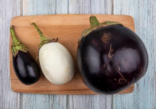 Bovenaanzicht van aubergines op snijplank op houten achtergrond