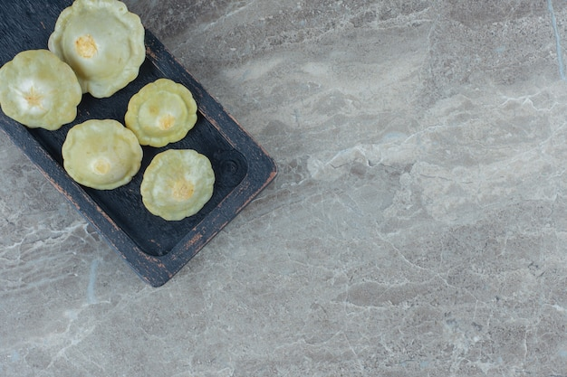 Bovenaanzicht van augurk green patty pan squash op een houten bord. Gratis Foto
