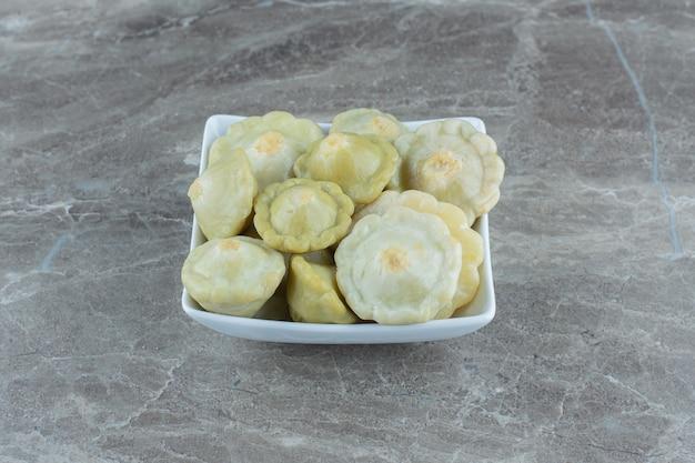 Bovenaanzicht van augurk groene patty pan squash in witte kom