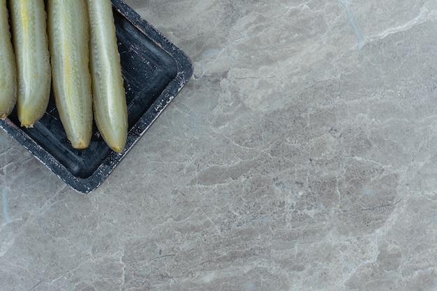 Bovenaanzicht van augurk plakjes op zwarte plaat.
