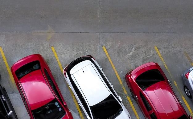 Bovenaanzicht van auto geparkeerd op betonnen auto parkeerplaats met gele lijn van verkeersbord op straat.