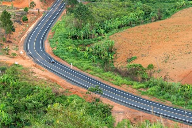 Bovenaanzicht van auto op geen autoweg op een achtergrond van groen bos en uitlopers