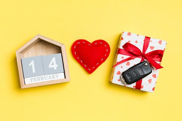 Bovenaanzicht van autosleutel op een geschenkdoos, rood textiel hart en feestelijke kalender op geel