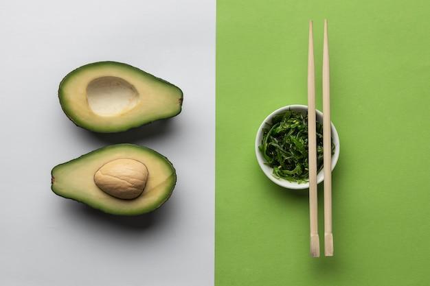 Bovenaanzicht van avocado met kom met groenen