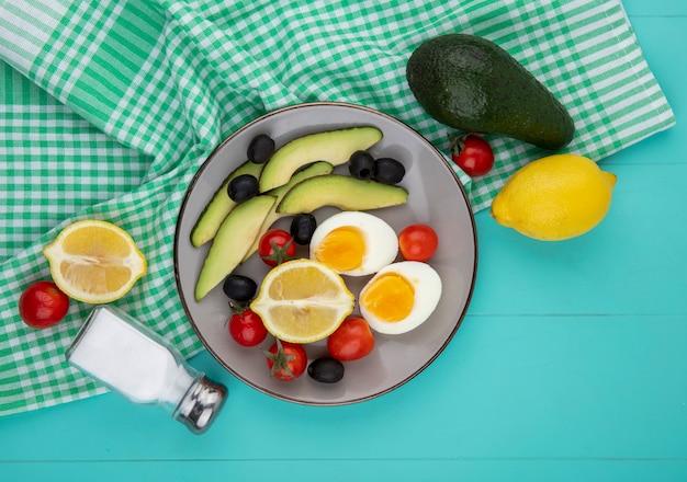 Bovenaanzicht van avocado op kom met citroentomaten olijven met zoutvaatje op groen tafellaken op blauw