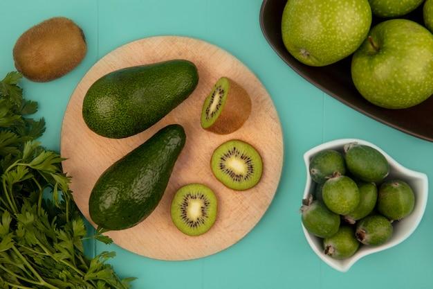 Bovenaanzicht van avocado's met plakjes kiwi op een houten keukenbord met feijoas op een kom met appels op een kom op een blauwe muur