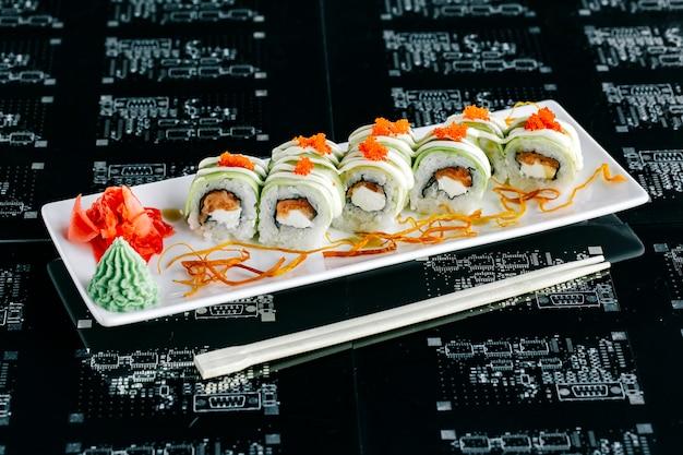 Bovenaanzicht van avocado sushi rolt met zalm gegarneerd met rode tobiko