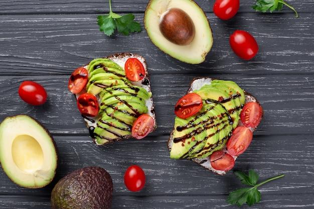 Bovenaanzicht van avocado toast met tomaten en saus