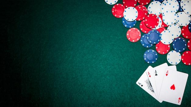 Bovenaanzicht van azen en casino chips op groene pokertafel