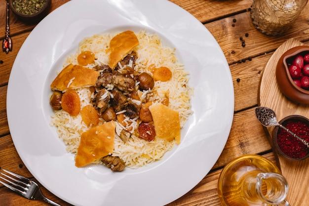 Bovenaanzicht van azerbeidzjaans pilaf rijst gekookt met lamsvlees en gedroogde vruchten gegarneerd met gazmag