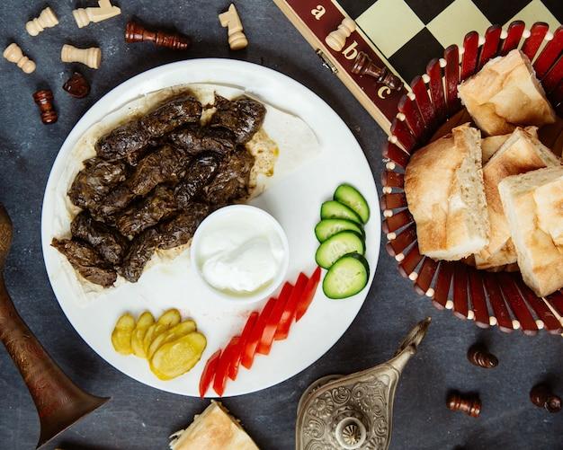 Bovenaanzicht van azerbeidzjaanse druivenbladeren dolma geserveerd met yoghurt groenten en augurken