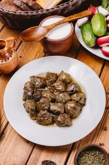 Bovenaanzicht van azerbeidzjaanse druivenbladeren dolma plaat geserveerd met yoghurt en salade