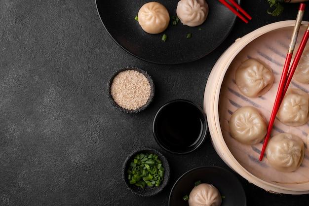 Bovenaanzicht van aziatische dumplings met stokjes, kruiden en kopie ruimte