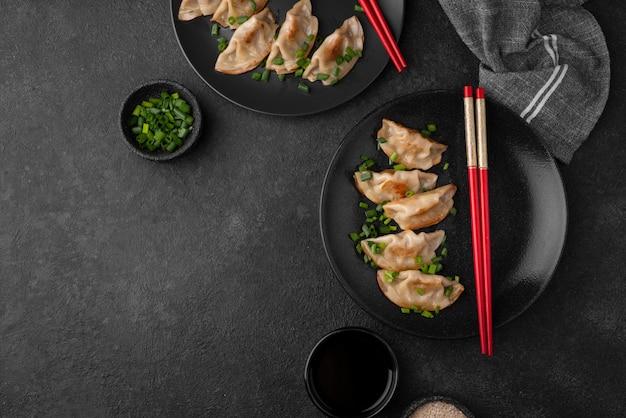 Bovenaanzicht van aziatische dumplings schotel met kruiden