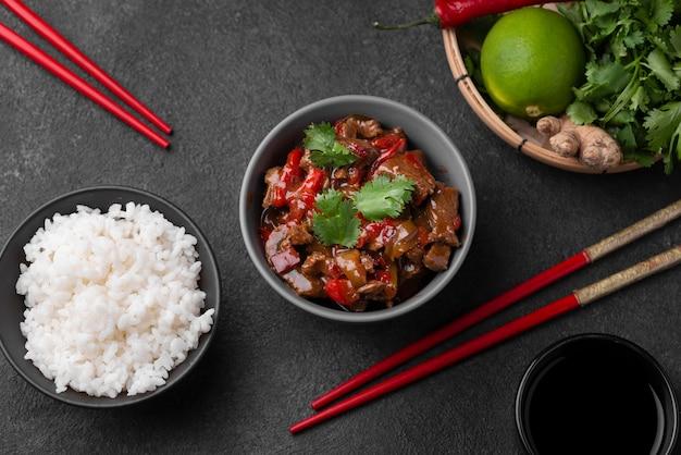 Bovenaanzicht van aziatische schotel met rijst en eetstokjes
