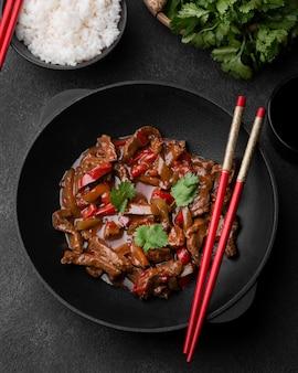 Bovenaanzicht van aziatische schotel met rijst en kruiden