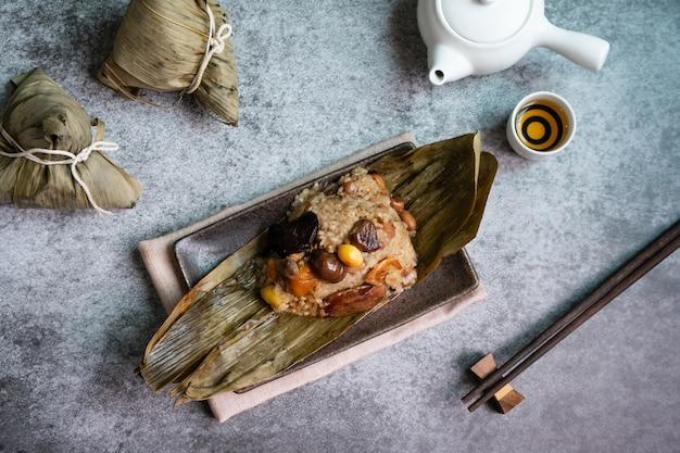 Bovenaanzicht van aziatische smakelijke zelfgemaakte gerechten in drakenboot (duan wu) festival, rijst knoedels of zongzi verpakt door gedroogde bamboebladeren op plaat met thee op zwarte bord