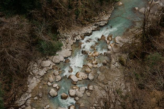 Bovenaanzicht van azuurblauwe bos rivier stroomt tussen rotsen in martvili canyon