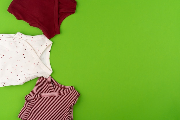 Bovenaanzicht van babykleding op groene ondergrond