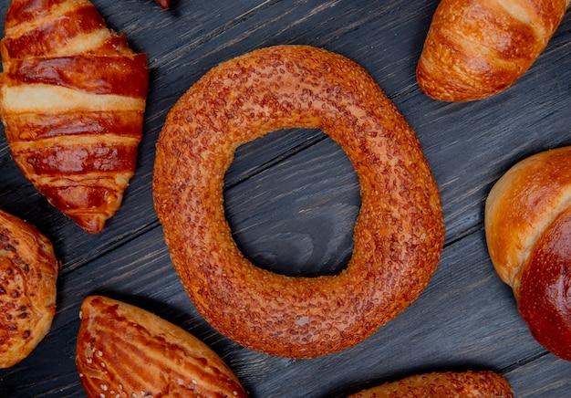 Bovenaanzicht van bagel en andere bakkerijproducten rond op houten achtergrond