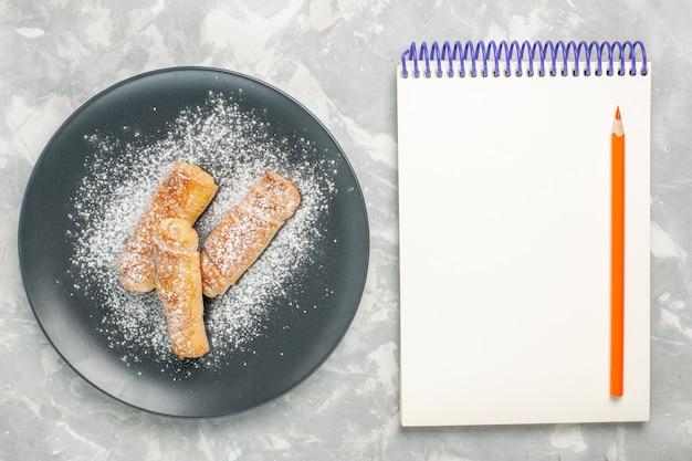 Bovenaanzicht van bagels met suiker in poedervorm met kladblok op wit oppervlak
