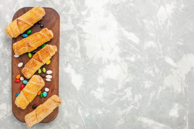 Bovenaanzicht van bagels met suiker in poedervorm met snoepjes op wit bureau