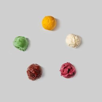 Bovenaanzicht van ballen van ijs - witte vanille, bruine chocolade, groene munt, gele mango, rode bes op een witte achtergrond. plat leggen.