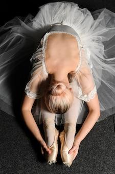 Bovenaanzicht van ballerina in tutu jurk die zich uitstrekt
