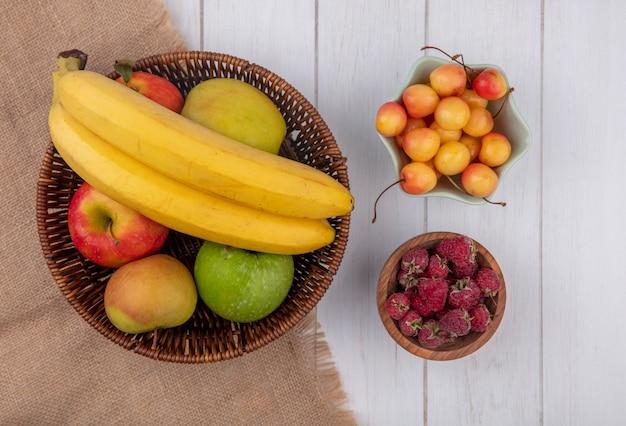 Bovenaanzicht van bananen met appels in een mand en witte kersen met frambozen in kommen op een wit oppervlak