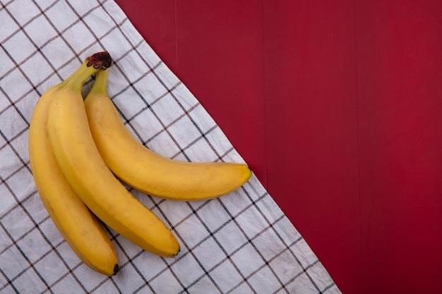 Bovenaanzicht van bananen op een geruite handdoek op een rode ondergrond