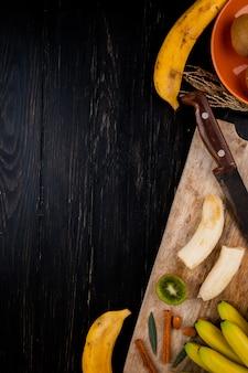Bovenaanzicht van bananenfruit met amandel, kaneelstokjes en oude keukenmes op een houten snijplank op zwart met kopie ruimte