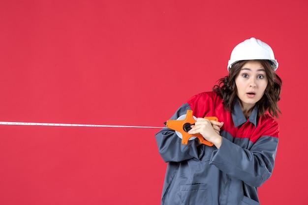Bovenaanzicht van bang vrouwelijke architect in uniform met harde hoed opening meetlint op geïsoleerde rode achtergrond