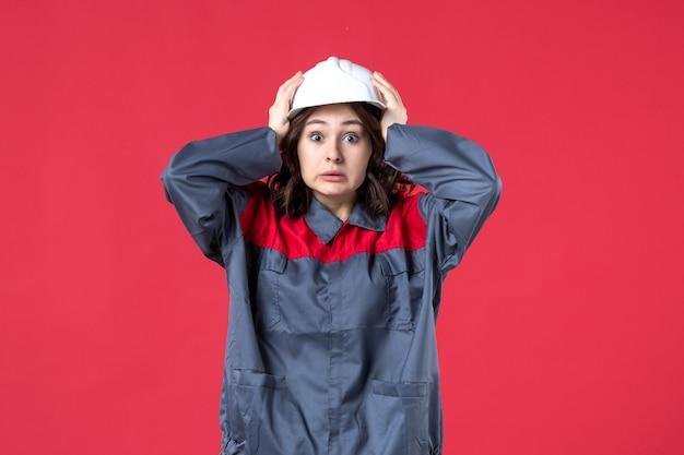 Bovenaanzicht van bang vrouwelijke bouwer in uniform met harde hoed op geïsoleerde rode achtergrond