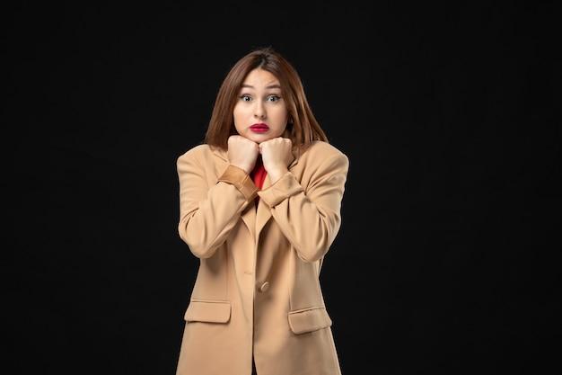 Bovenaanzicht van bange jonge vrouw in een lichtbruin pak poseren voor de camera op dark