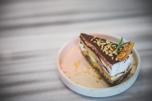 Bovenaanzicht van banoffee, zoete en heerlijke zelfgemaakte bekery, een fluitje van een cent, recept gemaakt van bananen, room, chocolade en een dikke karamelsaus. gebak op hout achtergrond