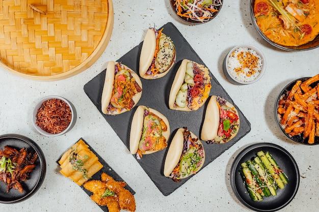 Bovenaanzicht van bao-broodjes omringd door verschillende gerechten op een witte tafel