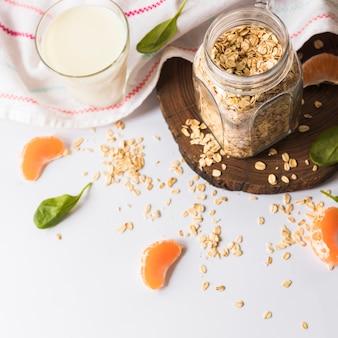 Bovenaanzicht van basilicumbladeren; stukjes sinaasappel; haver; melk en servet op witte achtergrond