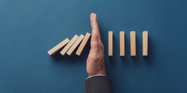 Bovenaanzicht van bedrijfscrisismanager die voorkomen dat vallende dominostenen instorten.