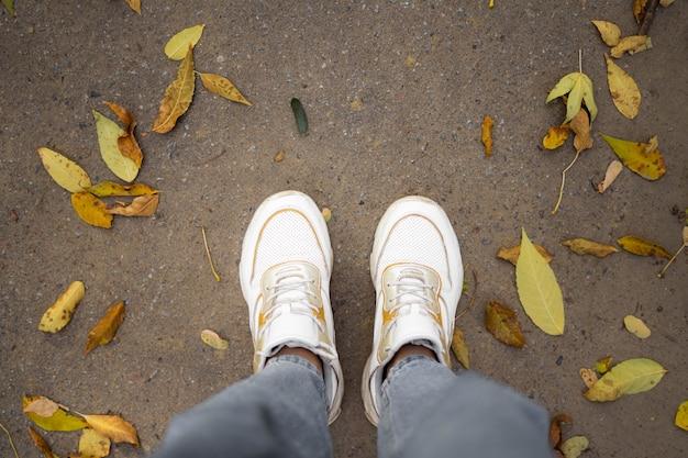 Bovenaanzicht van benen in witte sneakers op weg met gele bladeren.