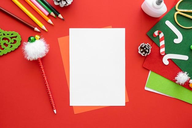 Bovenaanzicht van benodigdheden voor het maken van kerstcadeaus met papier en potloden