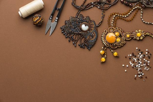 Bovenaanzicht van benodigdheden voor het werken met kralen met draad en schaar
