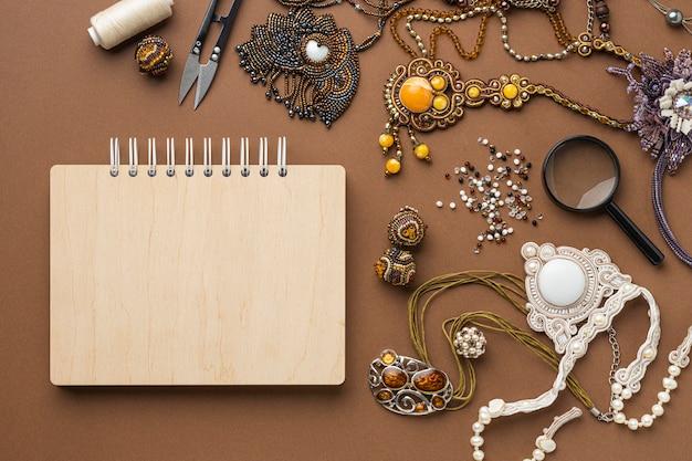 Bovenaanzicht van benodigdheden voor het werken met kralen met een notitieboekje