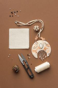 Bovenaanzicht van benodigdheden voor het werken met kralen met schaar en draad