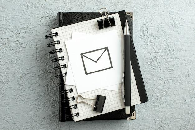 Bovenaanzicht van bericht puttend uit wit blad pen op spiraal notebook en boek op grijze zand achtergrond